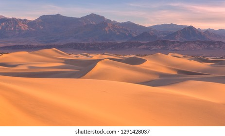 Waves of sand on top of the dunes at Sunrise in Mesquite flat sand dunes, Death Valley National Park, California, USA.