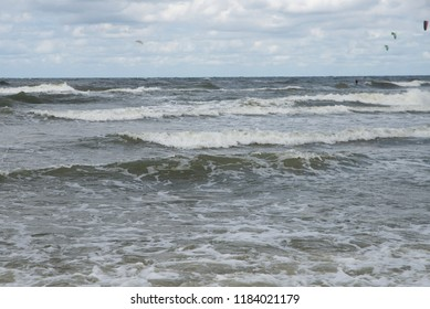 waves at sea and kitesurfing in the background