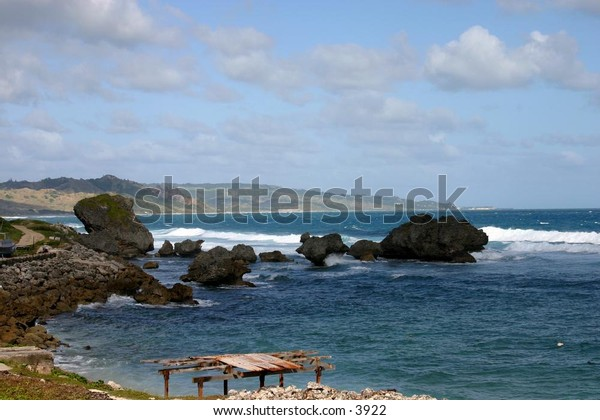 waves splash against huge boulders near shoreline
