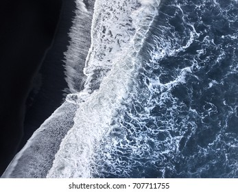 Waves splashing in at a black sand beach in Iceland.