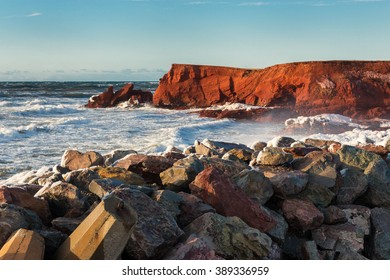 Waves splashing on beautiful red cliffs of Magdalen Islands during a winter sunset, Quebec, Canada