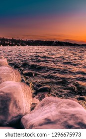 Waves splashing on ice covered rocks at Lake Geneva, Wisconsin while the sun sets over the water dying the sky warm tones of oranges and pinks and dimming blues.