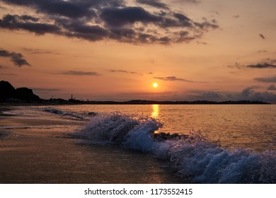 Waves splashing on the shore in the sunrise light with sun in the background and cloudy sky