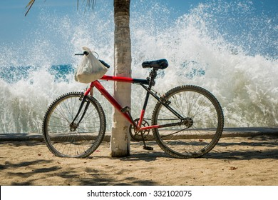 Waves splashing red bicycle leaning on palm tree in the beach, Santa Marta, Colombia