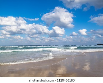 Waves spreading on a sandy Bulgarian coastline Black Sea beach, cloud reflections on the sand, beautiful cumulus clouds in the sky, at the seaside resort of Primorsko
