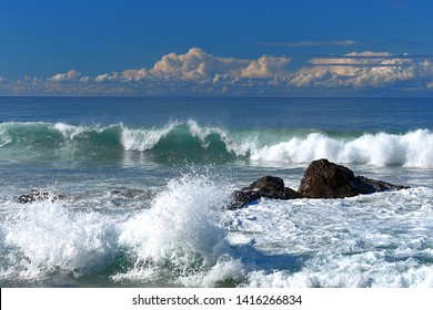 Waves and surf breaking over submerged rocks at Pebbly Beach Australia