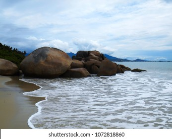 waves touching gently on the sands of the left tip of De Cima beach that has round rocks that delimit it, Pinheira, SC, Brazil