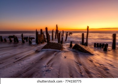 Waves wash down the beach and old coastal defenses at Spurn Point in Yorkshire