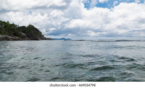 Waves with white foam rolled on shore with large rocks and tropical rostitelnostyu Seychelles and cloudy