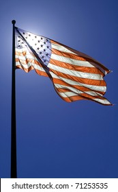 waving american flag, clear blue sky, sun is directly behind the flag
