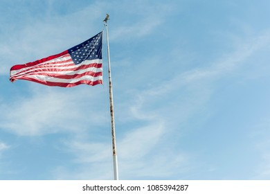 waving American flag on a white pylon with eagle on top against blue sky