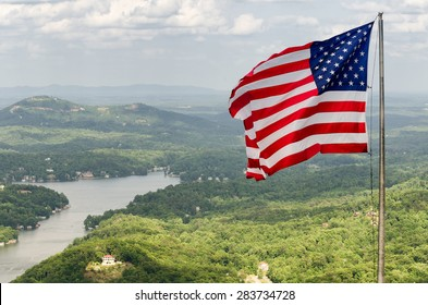 Waving american flag and view at the Lake Lure from the top of Chimney rock mountain, North Carolina, USA