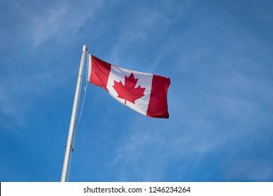 Waving Canadian flag against the blue sky.