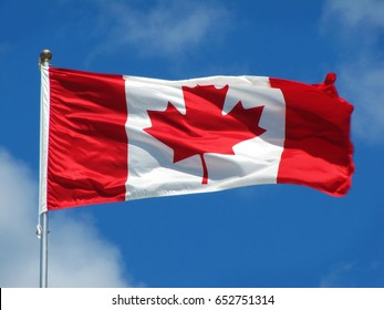 Waving Canadian flag against the blue sky