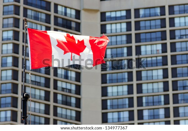Waving canadian flag and building in the background