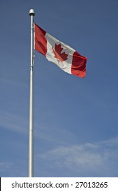 waving canadian flag on steel post, blue almost cloudless sky