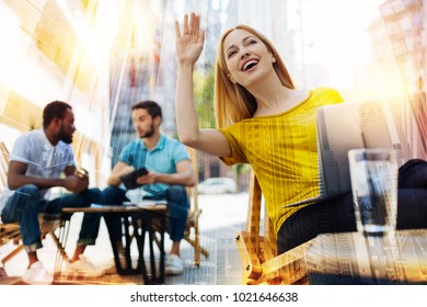 Waving. Cheerful young friendly woman feeling glad and waving while sitting in a cafe and noticing her fellow student in a crowd