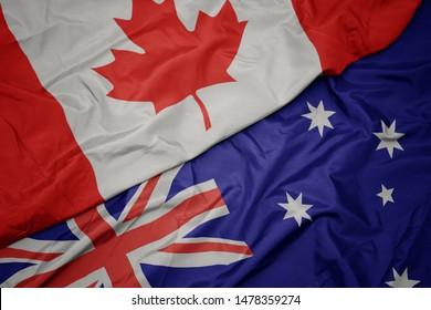 waving colorful flag of australia and national flag of canada. macro