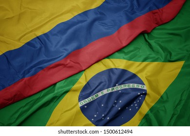 waving colorful flag of brazil and national flag of colombia. macro