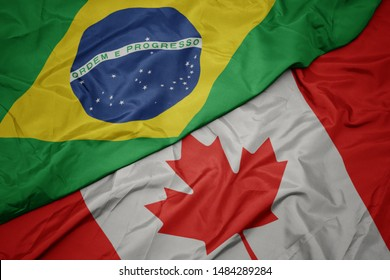 waving colorful flag of canada and national flag of brazil. macro