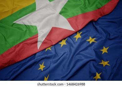 waving colorful flag of european union and flag of myanmar.macro