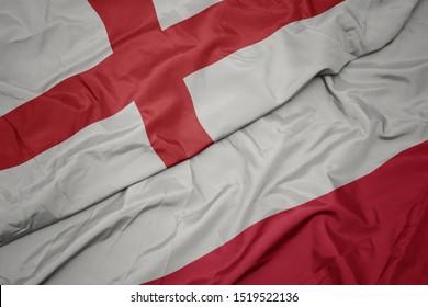 waving colorful flag of poland and national flag of england. macro