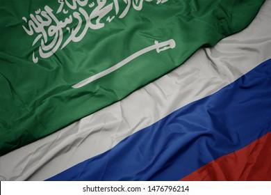 waving colorful flag of russia and national flag of saudi arabia. macro
