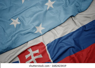 waving colorful flag of slovakia and national flag of Federated States of Micronesia . macro
