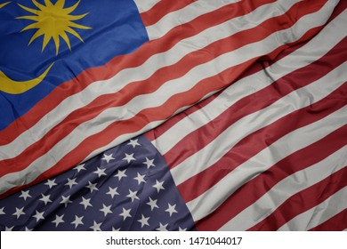waving colorful flag of united states of america and national flag of malaysia. macro
