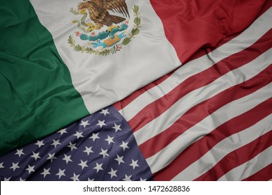 waving colorful flag of united states of america and national flag of mexico.