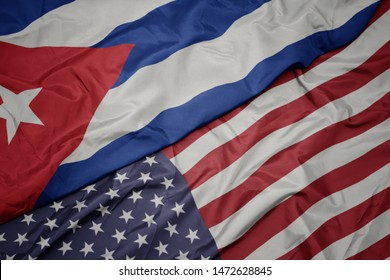 waving colorful flag of united states of america and national flag of cuba.