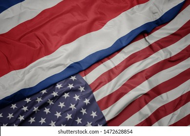 waving colorful flag of united states of america and national flag of costa rica.