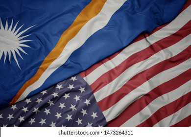 waving colorful flag of united states of america and national flag of Marshall Islands.