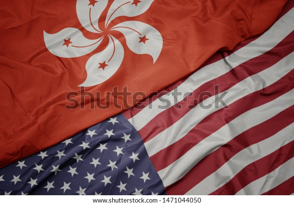 waving colorful flag of united states of america and national flag of hong kong.macro