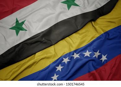 waving colorful flag of venezuela and national flag of syria. macro