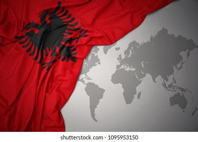 waving colorful national flag of albania on a gray world map background.