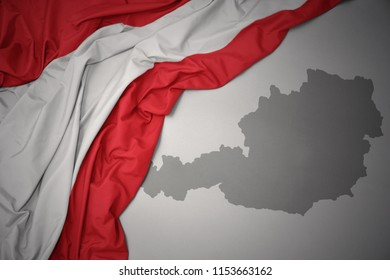 waving colorful national flag of austria on a gray map background.