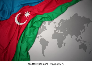 waving colorful national flag of azerbaijan on a gray world map background.