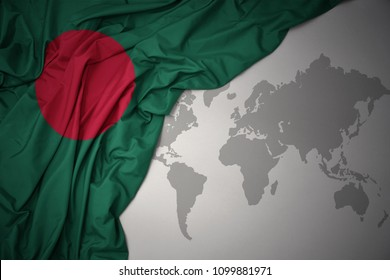 waving colorful national flag of bangladesh on a gray world map background.