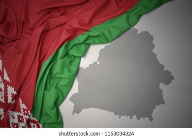 waving colorful national flag of belarus on a gray map background.