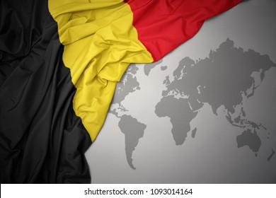 waving colorful national flag of belgium on a gray world map background.