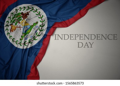 waving colorful national flag of belize on a gray background with text independence day. concept
