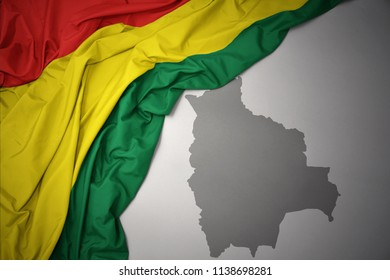 waving colorful national flag of bolivia on a gray map background.