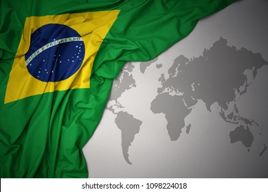 waving colorful national flag of brazil on a gray world map background.