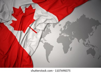 waving colorful national flag of canada on a gray world map background.