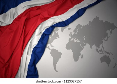 waving colorful national flag of costa rica on a gray world map background.