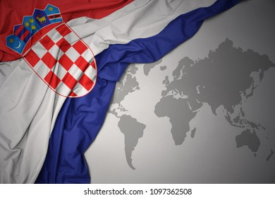 waving colorful national flag of croatia on a gray world map background.
