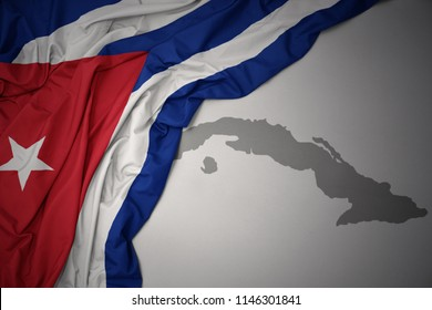 waving colorful national flag of cuba on a gray map background.