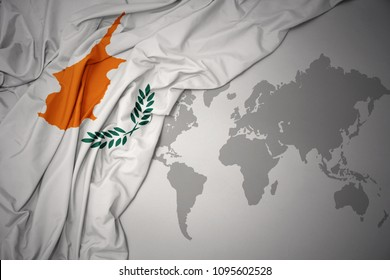 waving colorful national flag of cyprus on a gray world map background.