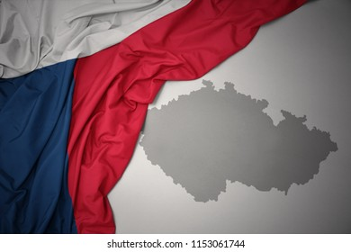 waving colorful national flag of czech republic on a gray map background.